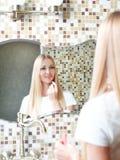 Junge Frau, die den Lippenstift betrachtet Spiegel anwendet Lizenzfreies Stockbild