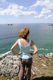 Junge Frau, die den Ozean überwacht Stockfotografie