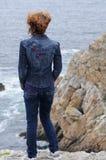 Junge Frau, die den Ozean überwacht Lizenzfreie Stockfotos