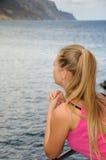 Junge Frau, die den Ozean auf einem Geländer aufpasst Stockbilder