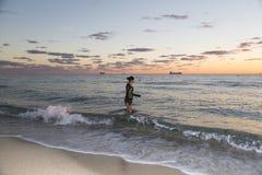 Junge Frau, die in den Ozean geht Lizenzfreie Stockbilder
