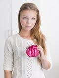 Junge Frau, die den rosafarbenen Fonds schaut bemüht anhält Lizenzfreie Stockfotos