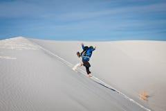 Junge Frau, die in den Sand springt Lizenzfreies Stockbild