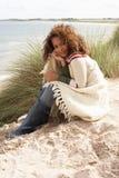 Junge Frau, die in den Sanddünen sitzt Stockfoto