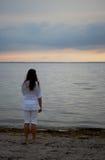 Junge Frau, die den Sonnenuntergang überwacht Lizenzfreie Stockfotos