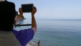Junge Frau, die den Sonnenuntergang auf der Tablette fotografiert stock video footage