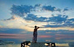 Junge Frau, die den Sonnenuntergang auf Seeküste aufpasst Lizenzfreies Stockfoto