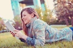Junge Frau, die den Tablet-Computer draußen legt auf Gras in einem Stadtpark verwendet stockbilder