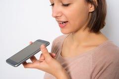 Junge Frau, die den vernehmbaren Assistenten des Telefons lokalisiert auf weißem backgr verwendet stockfoto
