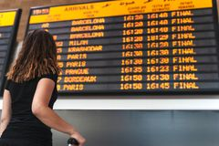 Junge Frau, die den Zeitplan am Flughafen überprüft lizenzfreie stockbilder