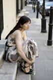 Junge Frau, die an der alten Tür sitzt Lizenzfreies Stockfoto