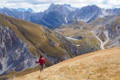 Junge Frau, die in der breiten Berglandschaft wandert lizenzfreie stockfotografie