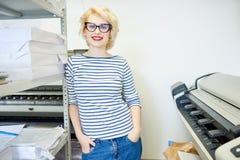 Junge Frau, die in der Druckerei aufwirft lizenzfreie stockfotografie
