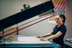 Junge Frau, die in der Druckfabrik arbeitet stockbild