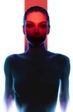 Junge Frau, die in der Dunkelheit mit rotem Licht aufwirft Stockfotografie