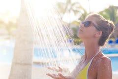 Junge Frau, die in der Dusche nahe Pool erneuert Stockfoto