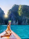 Junge Frau, die an der Front von longtail Boot kreuzender Phi Phi Leh Island, Krabi-Provinz, Thailand sitzt stockbilder