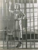 Junge Frau, die in der Gefängniszelle steht Stockfoto