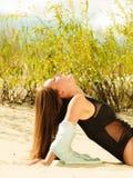 Junge Frau, die in der grasartigen Düne aufwirft Lizenzfreies Stockbild