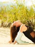 Junge Frau, die in der grasartigen Düne aufwirft Stockbilder