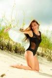 Junge Frau, die in der grasartigen Düne aufwirft Stockfoto