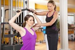 Junge Frau, die in der Gymnastik mit Kursleiter trainiert Lizenzfreie Stockfotos