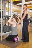 Junge Frau, die in der Gymnastik mit Kursleiter trainiert Lizenzfreies Stockbild