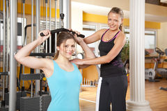 Junge Frau, die in der Gymnastik mit Kursleiter trainiert Stockfotos