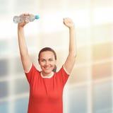 Junge Frau, die in der Hand Flasche über ihrem Kopf hält Hände oben Lizenzfreies Stockfoto