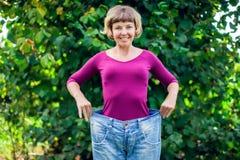 Junge Frau, die in der Hand große lose Jeans mit Gewicht des Apfels - trägt stockfotografie