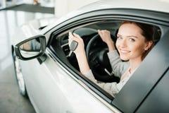 Junge Frau, die in der Hand im Neuwagen mit Schlüssel sitzt und an der Kamera lächelt Stockfotografie