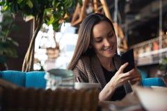 Junge Frau, die in der Hand mit Smartphone am Restaurant mit unscharfem Hintergrund lächelt stockbild
