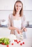 Junge Frau, die in der Küche kocht Stockfotos