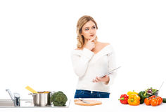Junge Frau, die in der Küche lokalisiert auf Weiß arbeitet Lizenzfreie Stockfotos