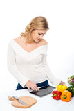 Junge Frau, die in der Küche lokalisiert auf Weiß kocht Lizenzfreie Stockfotografie
