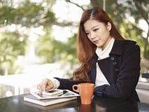 Junge Frau, die in der Kaffeestube denkt lizenzfreie stockfotografie