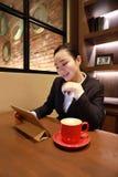Junge Frau, die in der Kaffeestube am Holztisch, an trinkendem Kaffee sitzt und Auflage verwendet Auf Tabelle ist Laptop Lizenzfreie Stockbilder