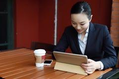 Junge Frau, die in der Kaffeestube am Holztisch, an trinkendem Kaffee sitzt und Auflage verwendet Auf Tabelle ist Laptop Lizenzfreies Stockfoto