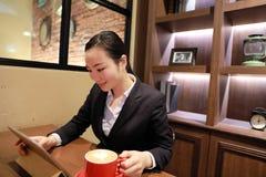 Junge Frau, die in der Kaffeestube am Holztisch, an trinkendem Kaffee sitzt und Auflage verwendet Auf Tabelle ist Laptop Lizenzfreie Stockfotografie