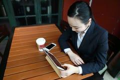 Junge Frau, die in der Kaffeestube am Holztisch, an trinkendem Kaffee sitzt und Auflage verwendet Auf Tabelle ist Laptop Lizenzfreies Stockbild
