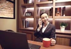Junge Frau, die in der Kaffeestube am Holztisch, an trinkendem Kaffee sitzt und Smartphone verwendet Auf Tabelle ist Laptop Stockbild