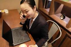 Junge Frau, die in der Kaffeestube am Holztisch, an trinkendem Kaffee sitzt und Smartphone verwendet Auf Tabelle ist Laptop Lizenzfreie Stockfotos