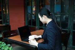 Junge Frau, die in der Kaffeestube am Holztisch, an trinkendem Kaffee sitzt und Smartphone verwendet Auf Tabelle ist Laptop Lizenzfreies Stockfoto