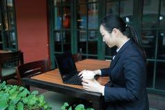 Junge Frau, die in der Kaffeestube am Holztisch, an trinkendem Kaffee sitzt und Smartphone verwendet Auf Tabelle ist Laptop Lizenzfreies Stockbild