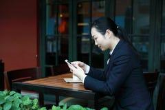 Junge Frau, die in der Kaffeestube am Holztisch, an trinkendem Kaffee sitzt und Smartphone verwendet Auf Tabelle ist Laptop Stockfotografie