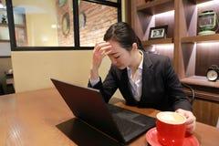 Junge Frau, die in der Kaffeestube am Holztisch, an trinkendem Kaffee und am besorgten Denken sitzt Auf Tabelle ist Laptop Stockfoto