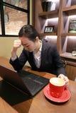 Junge Frau, die in der Kaffeestube am Holztisch, an trinkendem Kaffee und an denkendem Problem der Angst sitzt Auf Tabelle ist La Lizenzfreies Stockfoto