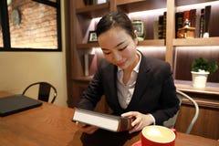 Junge Frau, die in der Kaffeestube am Holztisch, an trinkendem Kaffee und an gelesenem Buch sitzt Lizenzfreies Stockfoto