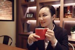 Junge Frau, die in der Kaffeestube am Holztisch, trinkender Kaffee sitzt Stockfoto