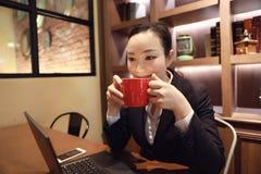 Junge Frau, die in der Kaffeestube am Holztisch, trinkender Kaffee sitzt Auf Tabelle ist Laptop Stockfotografie